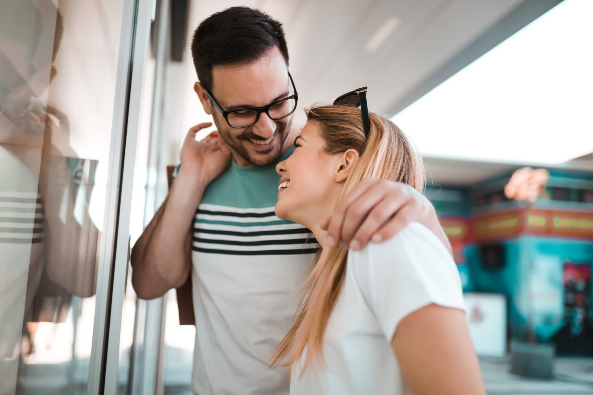 Portrait of happy couple with shopping bags who looking at shop window in a shopping mall